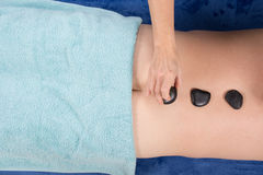 Bemannen Sie die Entspannung in einem Badekurortsalon mit heißen Steinen Stockfoto