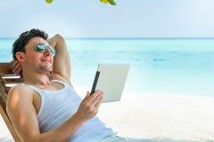 Bemannen Sie die Entspannung am Strand mit Tablette, Laptop Sehen Sie auf Maldives-Insel vom Flugzeug an Stockbilder