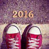 Bemannen Sie die Füße und hölzerne Zahlen, welche die Nr. 2016, als das neue bilden Stockbilder