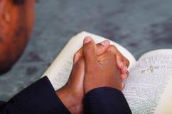 Bemannen Sie die faltenden Hände, die mit der offenen Bibel beten, die in der Front liegt, gesehen von hinten Modellkopf, Religio Stockfotos