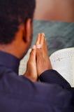 Bemannen Sie die faltenden Hände, die mit der offenen Bibel beten, die in der Front liegt, gesehen von hinten Modellkopf, Religio Stockfotografie