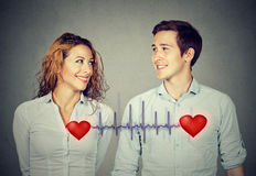 Bemannen Sie die Frau, die einander mit den roten Herzen betrachtet, die durch Kardiogramm verbunden werden Lizenzfreie Stockbilder