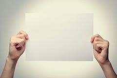 Bemannen Sie die Hände, die ein leeres Blatt Papier halten Stockbild
