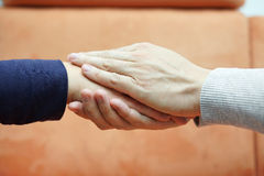 Bemannen Sie die Hände, die Frauenhand von beiden Seiten halten mitleid