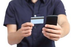 Bemannen Sie die Hände, die am intelligenten Telefon mit einer Kreditkarte kaufen stockfoto