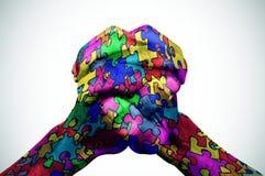 Bemannen Sie die Hände, die mit Puzzlespielstücken verschiedenen Farben kopiert werden Stockbilder