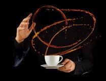 Bemannen Sie die Hände, die porcelaine Schale mit dem Spritzen der Flüssigkeit des Kaffees oder des Tees halten, lokalisiert auf  Stockfotos