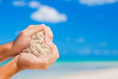 Bemannen Sie die Hände, die weißes tropisches Strandformherz halten Stockbilder