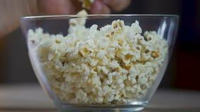 Bemannen Sie die Hände, die Popcorn von der Glasschüssel, aufpassenden von den Fernsehshows und vom Essen nehmen stock video footage