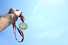 Bemannen Sie die Hand, die angehoben wird und Goldmedaille gegen skyl halten Preis- und Siegkonzept Selektiver Fokus Retro- Art-B Stockfoto