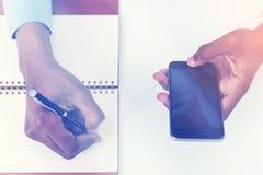 Bemannen Sie die Hand, die den Smartphone und Schreiben hält, getont Lizenzfreies Stockfoto