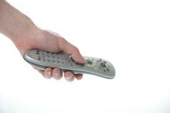 Bemannen Sie die Hand, die ein Fernsehfernsteuerungsüberweiß anhält Lizenzfreies Stockbild