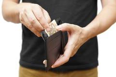 Bemannen Sie die Hand, die eine Geldbörse hält und Geld herausnimmt Lizenzfreie Stockbilder