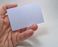 Bemannen Sie die Hand, die eine graue leere Anschlagtafel auf einem weißen Hintergrund hält Stockbilder
