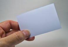 Bemannen Sie die Hand, die eine graue leere Karte auf einem weißen Hintergrund hält Lizenzfreie Stockfotografie