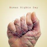 Bemannen Sie die Hand, die mit Draht und dem Menschenrechtstag des Textes gebunden wird Lizenzfreie Stockfotografie