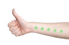 Bemannen Sie die Hand, die sich Daumen und die Bewertung mit fünf Sternen zeigt stockbilder