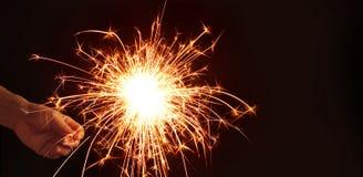 Bemannen Sie die Hand, die Wunderkerzefeuerwerk auf dunklem Nachthintergrund hält Stockfoto