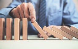 Bemannen Sie die Hand, die einen fallenden Domino-Effekt des Risikos stoppt lizenzfreie stockfotos