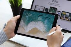 Bemannen Sie die Hand, die iPad Pro mit IOS 11 auf dem Schirm hält Stockfotografie