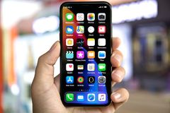 Bemannen Sie die Hand, die iPhone X mit Hauptschirm IOS hält Stockbilder