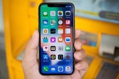 Bemannen Sie die Hand, die iPhone X mit Hauptschirm IOS hält Stockfotos