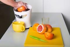Bemannen Sie die Herstellung des frischen Orangensaftes auf der Küche Lizenzfreie Stockfotos