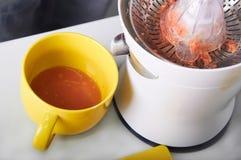 Bemannen Sie die Herstellung des frischen Orangensaftes auf der Küche Stockfotos