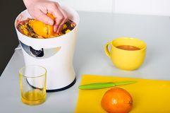Bemannen Sie die Herstellung des frischen Orangensaftes auf der Küche Lizenzfreies Stockfoto