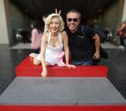 Bemannen Sie die Herstellung von Häschenohren hinter Marilyn Monroe-` s Kopf beim Mada lizenzfreies stockfoto
