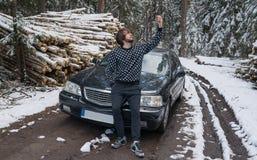 Bemannen Sie die Herstellung von selfie am Telefon nahe Auto im Winterwald stockfotos