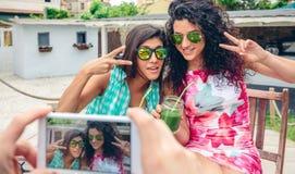 Bemannen Sie die Hände, die zwei Frauen mit grünen Smoothies Foto machen Stockfotos