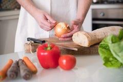 Bemannen Sie die Hände, die Zwiebelscheiben in der Küche schneiden Lizenzfreies Stockfoto