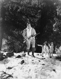 Bemannen Sie die Jagd im schneebedeckten Holz mit Hunden (alle dargestellten Personen sind nicht längeres lebendes und kein Zusta Stockfotos