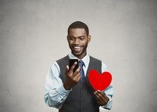 Bemannen Sie die Prüfung seines intelligenten Telefons und rotes Herz halten Stockbild