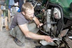 Bemannen Sie die Reparatur des Motorrades in der Garage, Nahaufnahme stockbild