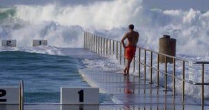 Bemannen Sie die Stellung, die große Wellen aufpasst, Ozeanbäder zu schlagen stock video footage