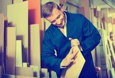 Bemannen Sie die tragende schützende Arbeitskleidung, die mit Sperrholz im Speicher steht Stockfotos