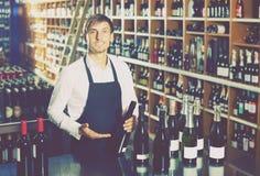 Bemannen Sie die tragende Uniform des Verkäufers, die Flasche Wein isst Stockbild