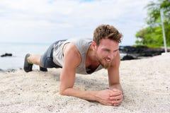 Bemannen Sie die Trainingskerneignung, die Planke auf Strand tut Stockbilder