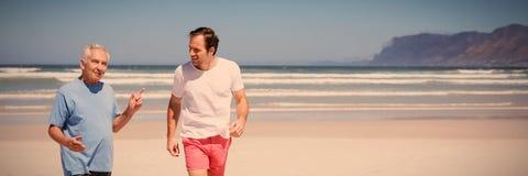 Bemannen Sie die Unterhaltung mit seinem Vater beim Gehen am Strand lizenzfreie stockfotos