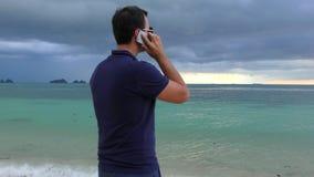 Bemannen Sie die Unterhaltung an seinem intelligenten Telefon auf dem Strand im bewölkten trüben Wetter stock video footage