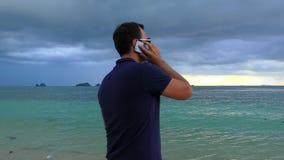 Bemannen Sie die Unterhaltung an seinem intelligenten Telefon auf dem Strand im bewölkten trüben Wetter stock footage