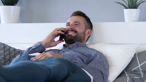 Bemannen Sie die Unterhaltung am Telefon beim Lügen im Bett stock video
