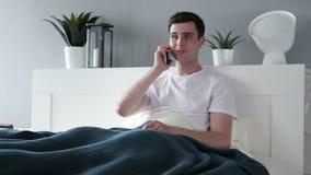 Bemannen Sie die Unterhaltung am Telefon beim Lügen im Bett stock footage