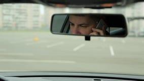 Bemannen Sie die Unterhaltung am Telefon in der Autospiegelansicht stock video footage