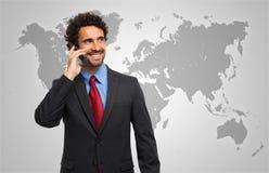 Bemannen Sie die Unterhaltung am Telefon vor einer Weltkarte Stockfotos