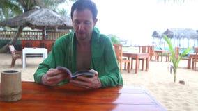 Bemannen Sie die Unterhaltung und das Ablesen eines Buches im Strandurlaubsort stock footage