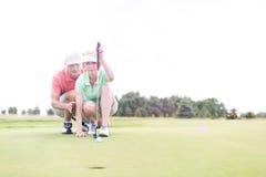 Bemannen Sie die Unterstützung der Frau, die Ball auf Golfplatz gegen klaren Himmel zielt Stockbilder