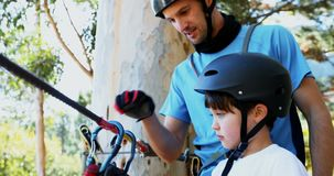 Bemannen Sie die Unterstützung des Kindes, um carabiner auf Ziplinie 4K 4k zu reparieren stock video footage